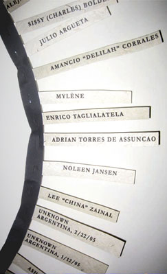A short section of ribbon with the names of ten trans victims attached