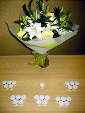 The focal point is a table with a vase of white lilies and roses, and 25 + 1 candles